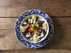 Versier salade met geitenkaas en tomaat